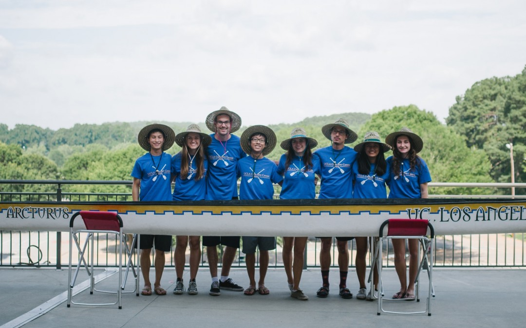 UCLA students in matching hats and shirts stand in front of concrete canoe