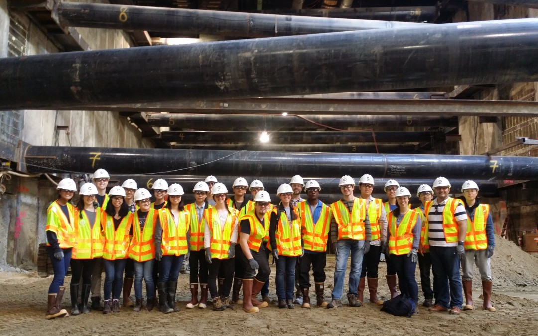 group of people in construction vests stand below large pipes