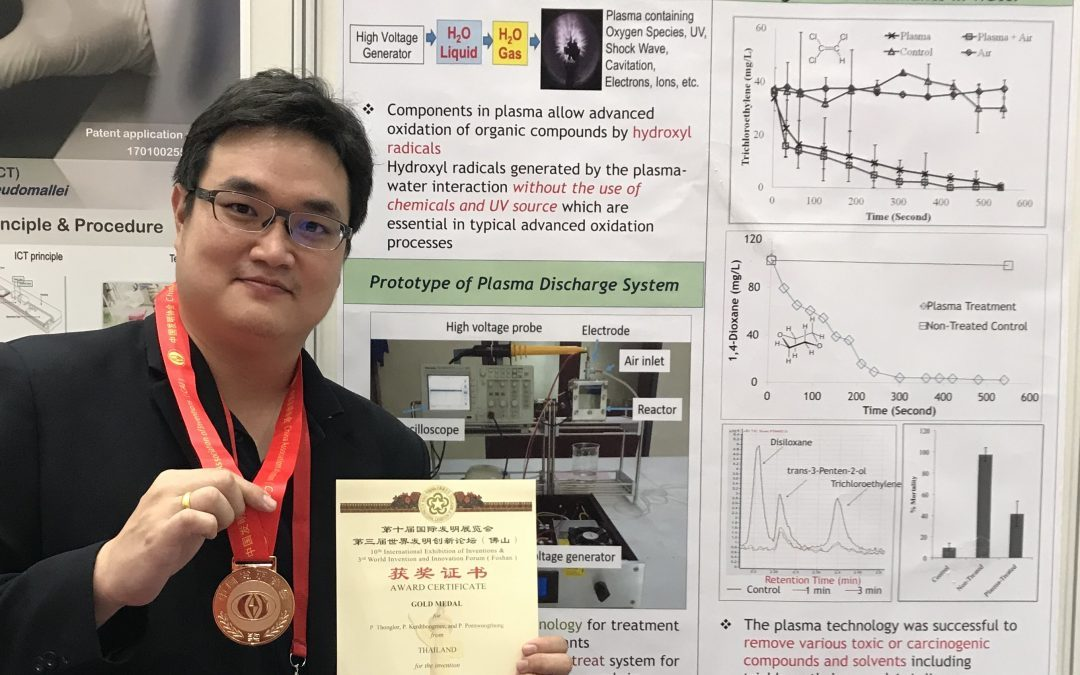 Dr. Peerapong wearing medal, holding Award Certificate, in front of a poster