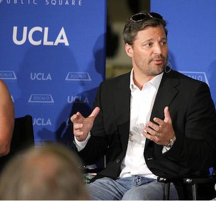 Erik Hoek speaking in front of UCLA logo