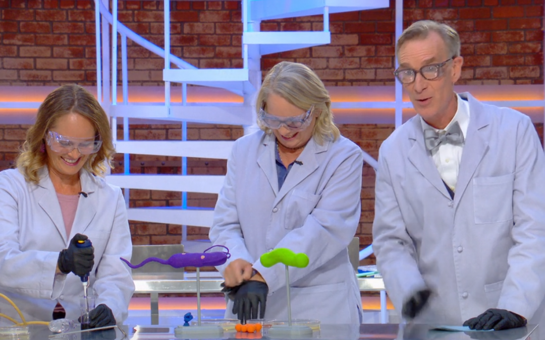 Bill Nye and two women in lab coats doing science experiment
