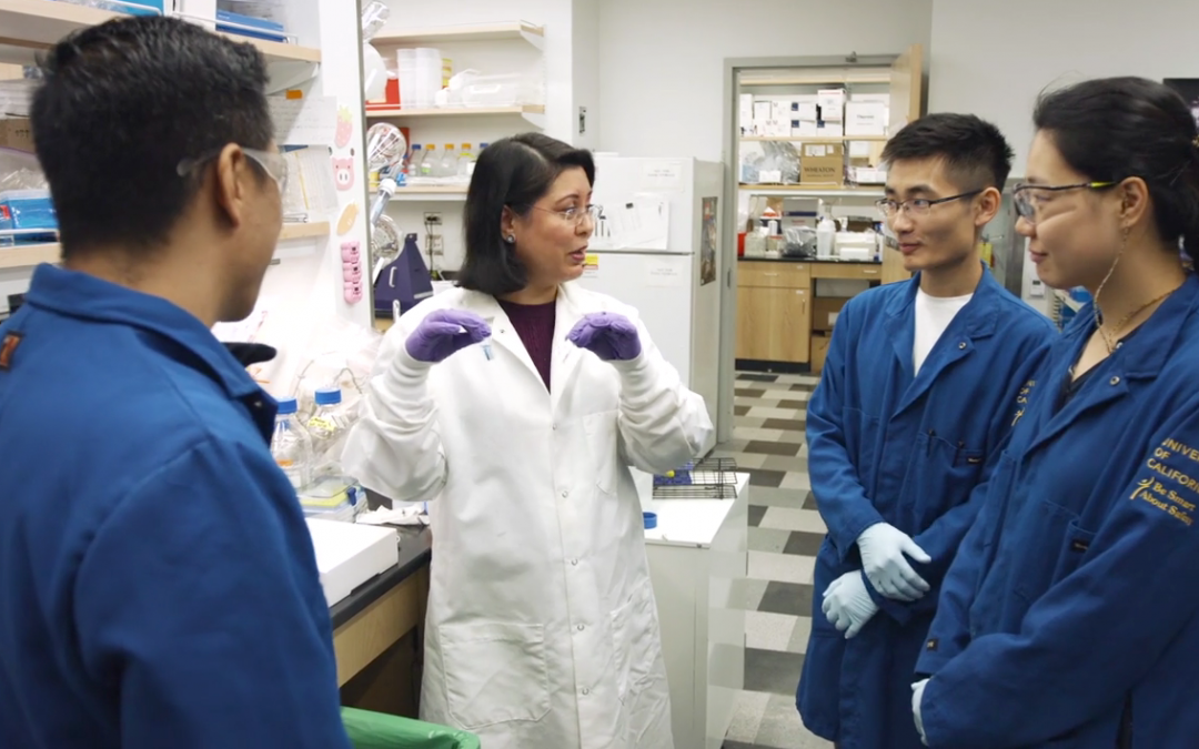 Mahendra speaks to three students in a lab