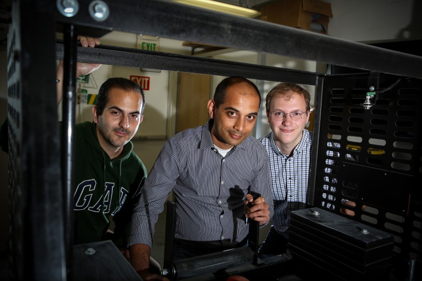 UCLA civil engineering professor Gaurav Sant is flanked by project scientists Iman Mehdipour, left, and Gabe Falzone behind a machine they use to make concrete bricks with recycled carbon. (Jason Armond/Los Angeles Times)
