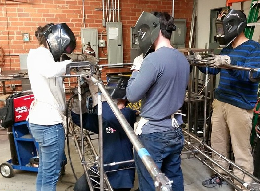 Students construct steel bridge outline with protective helmets and gloves on