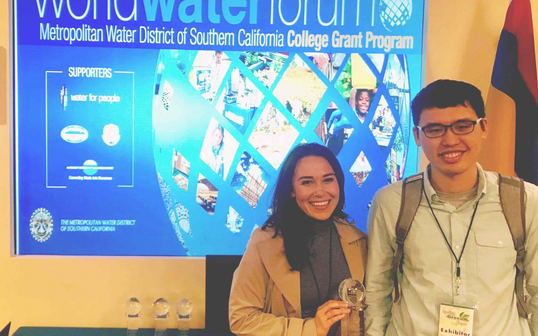 "young woman holds a clear award, standing next to a young man in glasses, in front of a blue poster that reads ""worldwaterforum Metropolitan Water District of Southern California College Grant Program"""