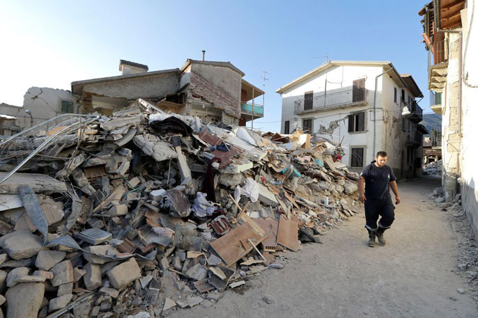 Man stands to the right of earthquake wreckage